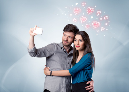 A young couple in love and drawn red hearts taking selfie with a mobile phone in the handsome guys hand in front of an empty clear grey wall background concept
