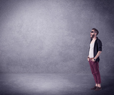 A hipster guy in stylish clothes shouting in front of an empty urban concrete wall background concept Stock Photo