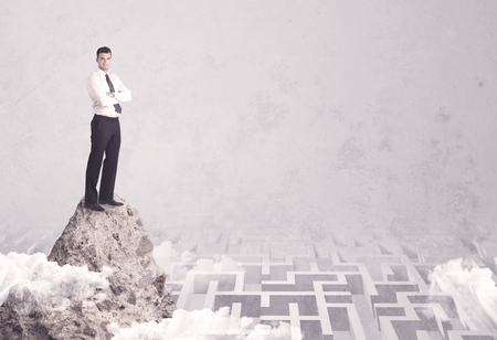 Maze is no challenge for successful businessman standing on top of a cliff as he is the best at solving problems concept Stock Photo