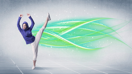A good looking fresh street dancer dancing in front of grey background with white and bright, colorful green lines concept Stock Photo