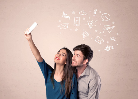 A young couple in love taking selfie with a mobile phone in the handsome guys hand and drawn media communication icons above them, confused ideas concept Stock Photo