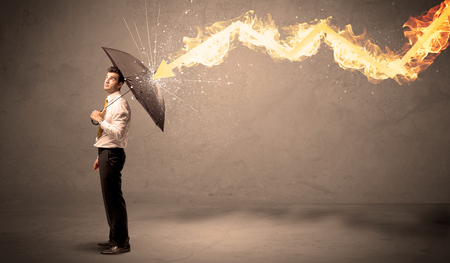 Business man defending himself from a fire arrow with an umbrella on grungy background Stock Photo