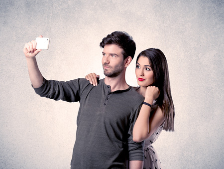 A young couple in love taking selfie with a mobile phone in the handsome guys hand in front of an empty clear grey wall background concept
