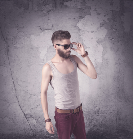 Funny vintage guy with long beard and stylish hair standing in front of urban concrete wall concept Stock Photo