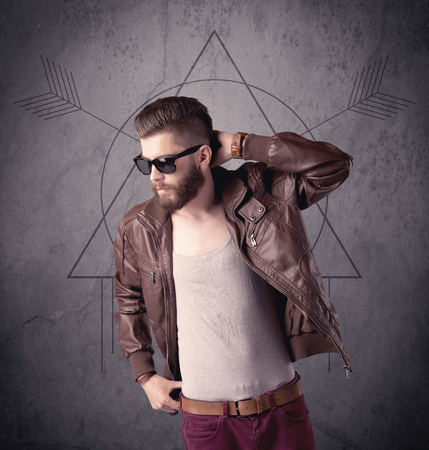 A young hipster male in modern clothes standing in front of an urban wall with modern sign illustration concept Stock Photo