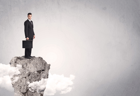 A happy successful businessman standing on a stone cliff with clouds in front of clear empty grey background concept Stock Photo