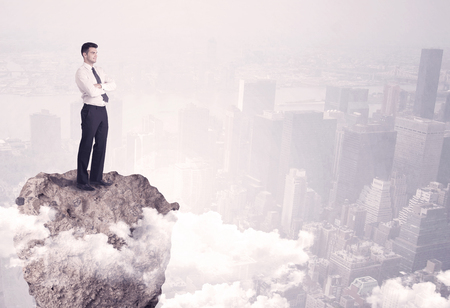 A young successful happy businessman standing confident on stone cliff in the clouds looking at the city scape from above concept