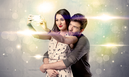 A fresh happy couple taking selfie photo with mobile phone in front of colorful lights glitter wall background concept Stock Photo