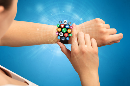 Hand with smartwatch and application symbols nearby.