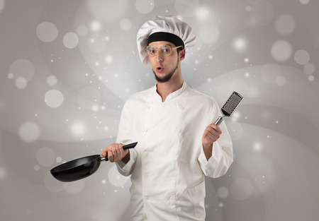 Male cook with kitchen tools and shiny grey wallpaper