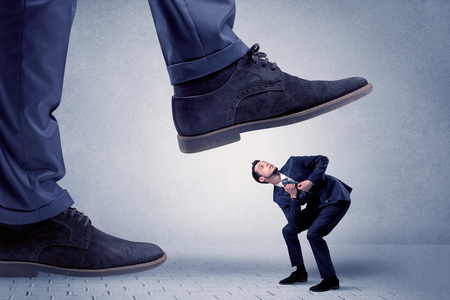 Young handsome businessman getting crushed by a big formal shoe Stock Photo