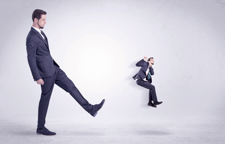 Big man in suit kicking out little himself out with simple white wallpaper 版權商用圖片