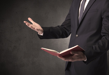 Businessman holding a book in his hand.