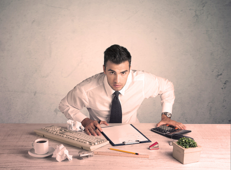 A young office worker sitting at desk working with keyboard, papers, highliter in front of empty clear background wall concept Banque d'images