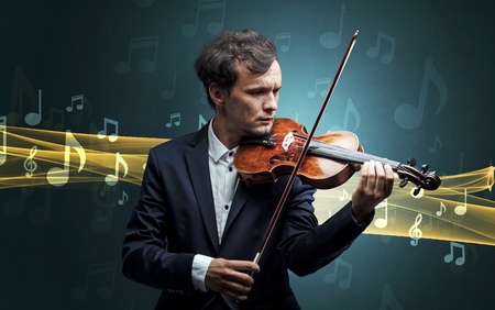 Young male musician playing on his violin with musical notes around