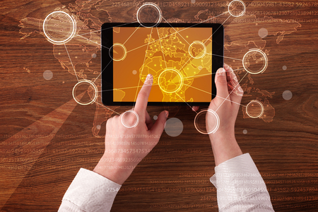 Caucasian business hands holding tablet with orange business-statistics screen Stock Photo
