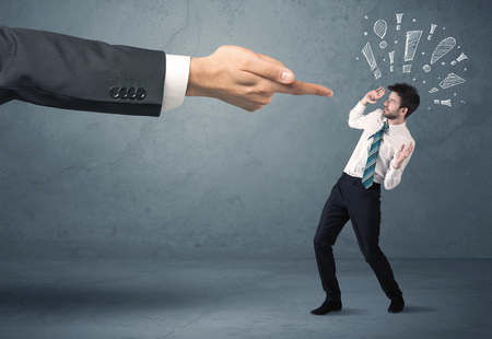 Employee in trouble getting last warning from boss concept with big business hand pointing at salesman and drawn exclamation marks Stock Photo