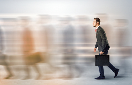 Young businessman with briefcase hurry up on a crowded street with blurred people around Archivio Fotografico