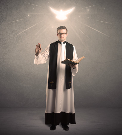A holy priest reading a prayer from the holy bible with illustrated glowing angel above his head concept. Archivio Fotografico