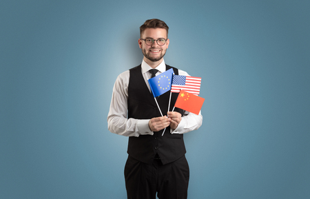 Cheerful student standing in front of wall with national flag on his hand 스톡 콘텐츠