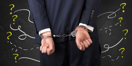 Now arrested men with handcuffs and chalk drawn question signs and lines around  Stock Photo