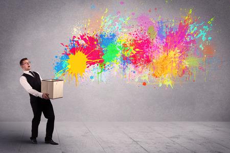 Een jong glimlachend bedrijfsmannetje die een kartonnen doos met illustratie van kleurrijke nevelverf plons op stedelijk muurconcept houden als achtergrond.