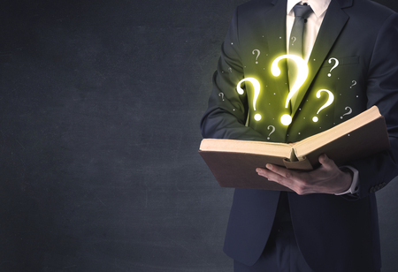 Businessman holding a book with question mark symbol. Foto de archivo