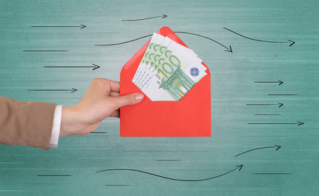 Female hand holding coloured and white envelope with green background and arrows around  Reklamní fotografie