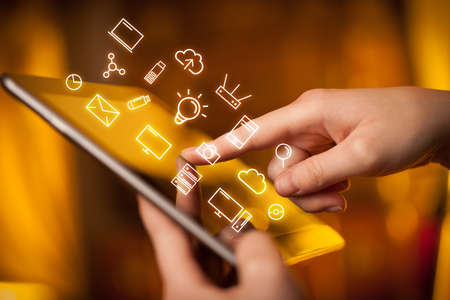 Female hands touching tablet with white technology related icons  Stock Photo
