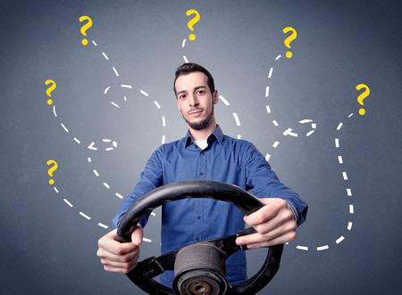 Young man holding black steering wheel with question marks around him 版權商用圖片