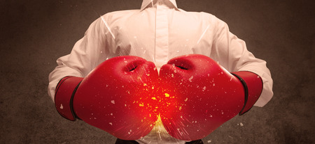 A strong sales person breaking something into pieces with red boxing gloves concept illustrated with glowing residue flying in the air. Reklamní fotografie