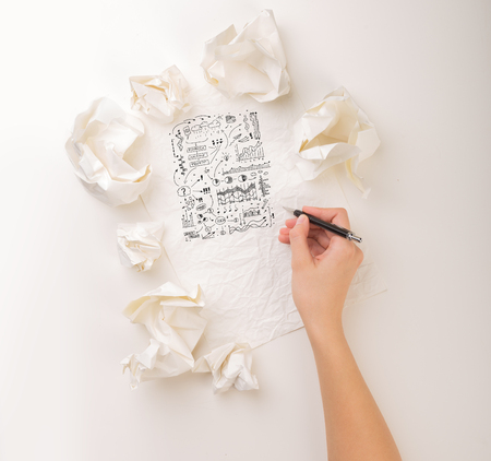 Female hand next to a few crumpled paper balls drawing charts and graphs Stock Photo
