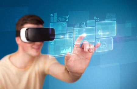 Young impressed man wearing virtual reality goggles with blue squares containing data at his fingers  Stock Photo