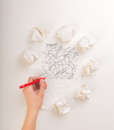 Female hand next to a few crumpled paper balls drawing random scribbles  Stock Photo