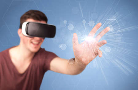 Young impressed man wearing virtual reality goggles with blue hexagons around him Stock fotó - 95879289