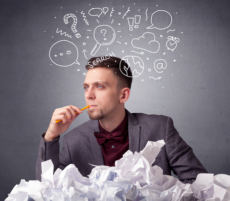 Young businessman sitting behind crumpled paper with mixed doodles over his head Stock Photo