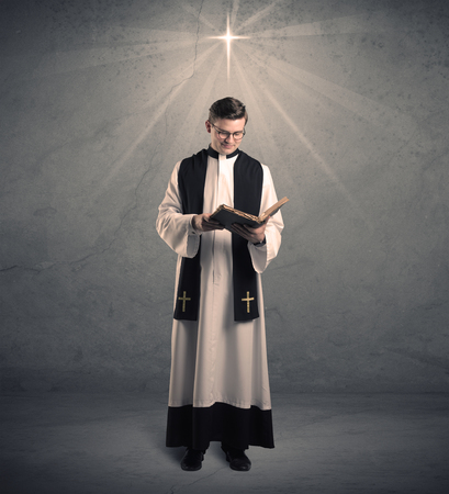 A young male priest in black and white giving his blessing in front of grey wall with glowing cross concept. Standard-Bild
