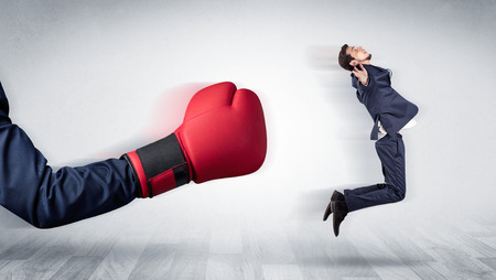 Big red boxing glove knocks out little businessman concept  Stock Photo