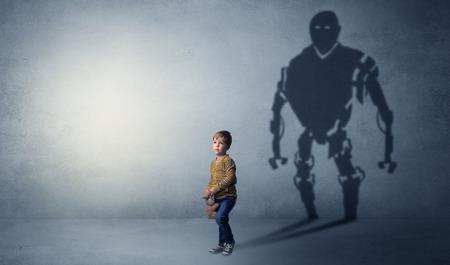Little boy's self image appear as a big robotman shadow on his background  Фото со стока