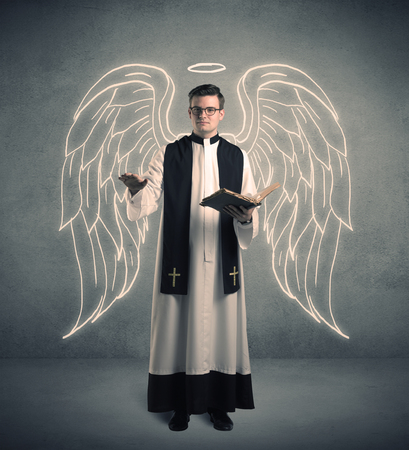A young male priest with drawn large angel wings standing with the holy bible in his hands concept.