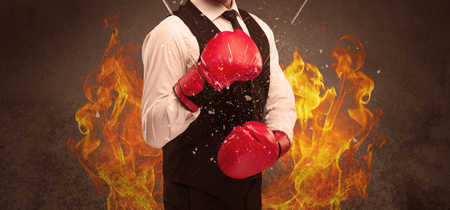 A strong sales person breaking something into pieces with red boxing gloves concept illustrated with glowing residue flying in the air. Stockfoto