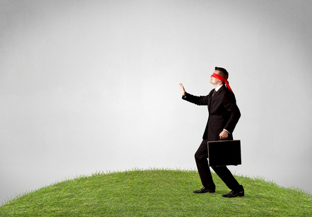 Young blindfolded businessman steps on a patch of grass Stock Photo