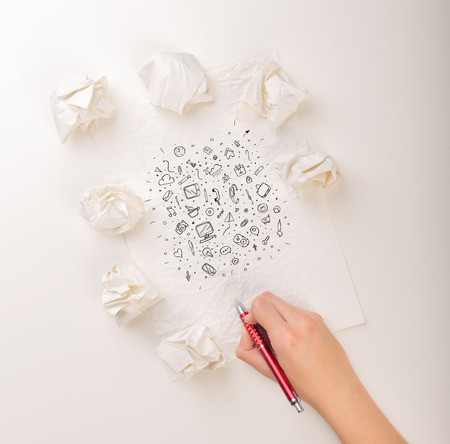 Female hand next to a few crumpled paper balls drawing mixed media icons 免版税图像