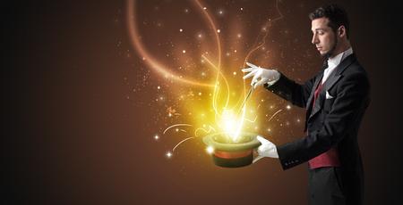 mago mano escribe con luz de la varita de un cilindro negro