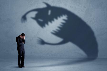 Biznes człowiek boi się własnej koncepcji potwora cienia na tle nieczysty