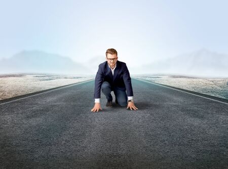 Young determined businessman kneeling before blank running track  Stock Photo