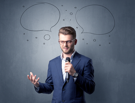 Businessman speaking into microphone with speech bubbles over his head