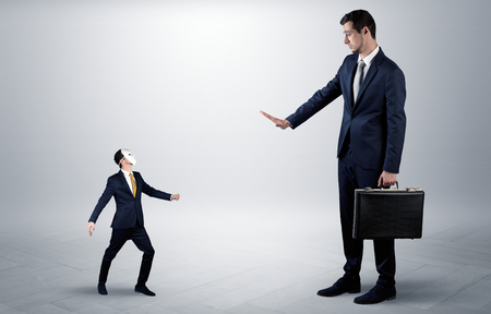 Conflict between small masked businessman and big elegant businessman  Stock Photo