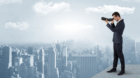 Businessman looking forward to a city  with binoculars from skyscraper concept  Stock Photo