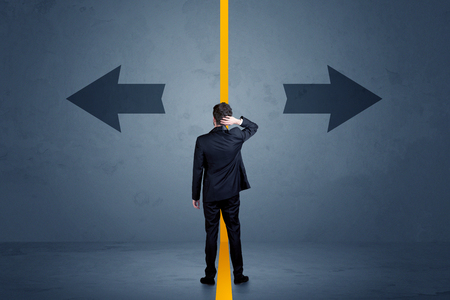 Business person choosing between two options separated by a yellow border arrow concept Foto de archivo